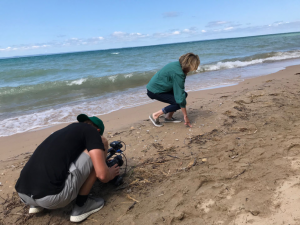 Amy Sherman helps producer Kyle Mattson get a closeup shot of picking up stones on the beach