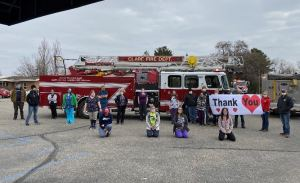 the Clare Fire Department parades past MediLodge's Clare location