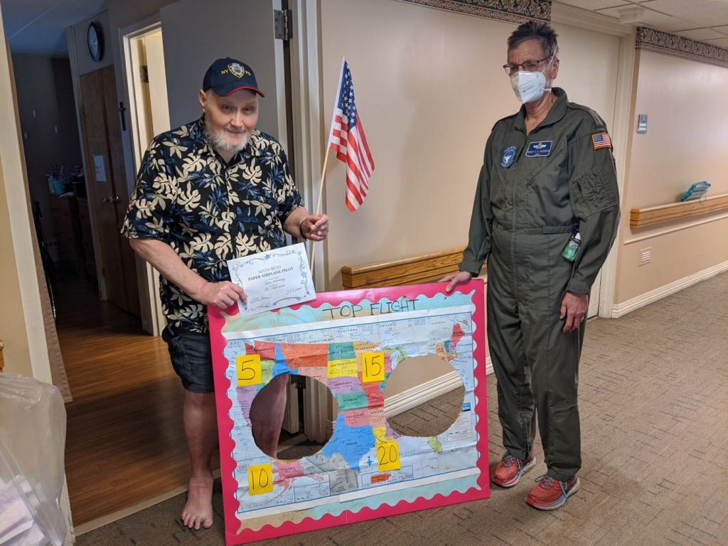 Residents at MediLodge at the Shore in Grand Haven made paper airplanes and then had a competition to see whose planes could fly through the holes in a plywood map of the USA.