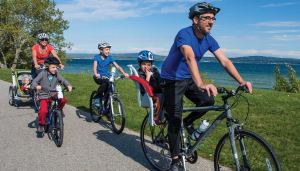 family with kids ride bikes along a trail in Petoskey, MI