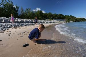 Boy hunts for Petoskey stones on a beach in Petoskey, MI