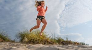 kid jumping on a beach dune