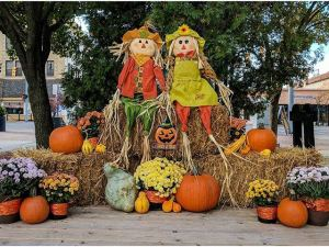 two silly scarecrows sitting on top of hay bales and pumpkins in a fall themed display