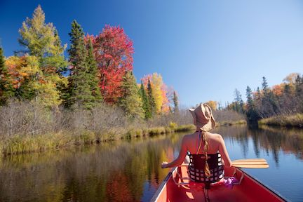 woman canoeing looking at fall colors