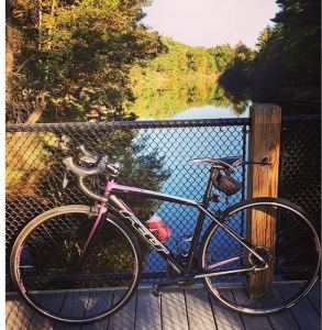 bicycle leaning against the railing of a bridge over a stream
