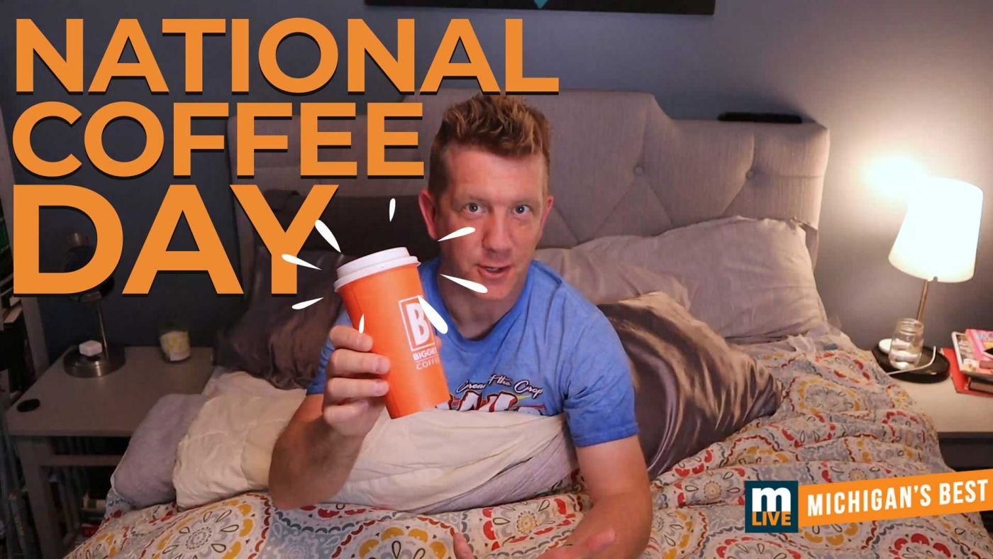 Eric Hultgren holding a Biggby coffee sitting in bed