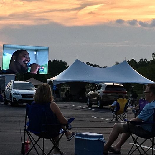 people watching a concert at a drive in movie theater