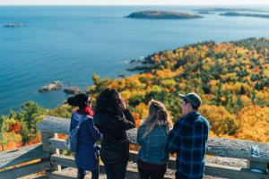 people standing at an overlook, viewing water and autumn trees
