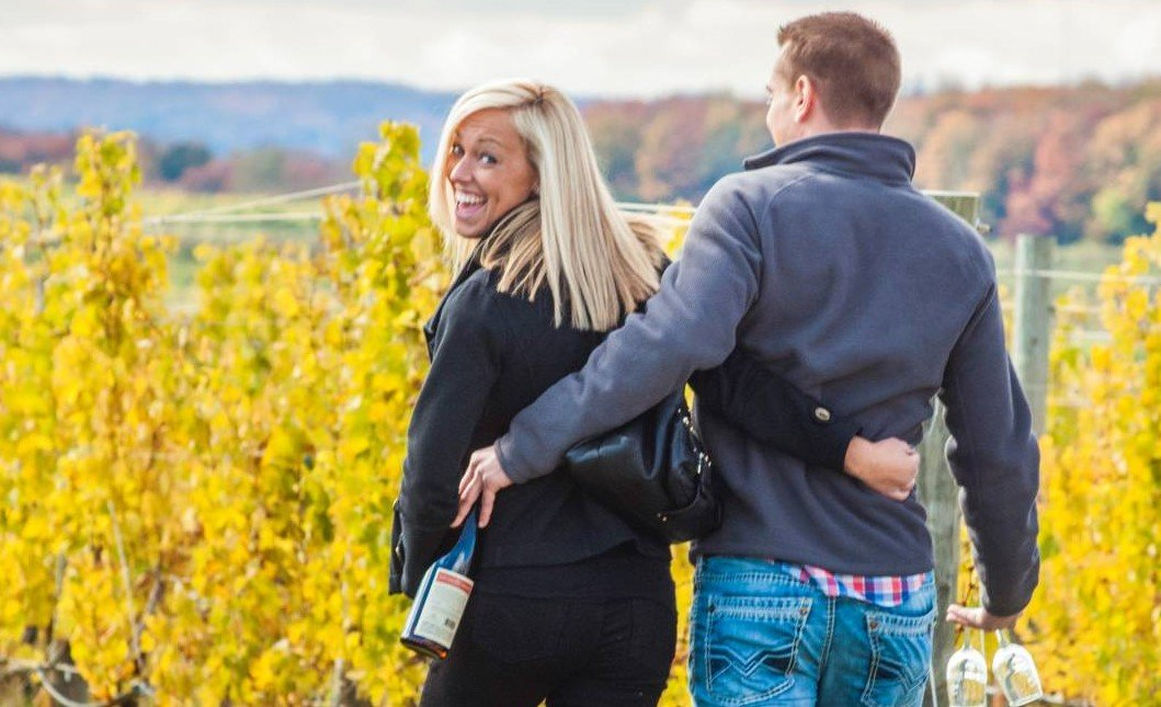 couple walking through a vineyard in Traverse City, MI