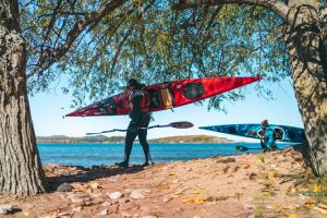 person carrying a kayak at Preque Isle in Marquette, MI