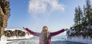 person standing in front of a beautiful winter lake scene throwing snow into the air