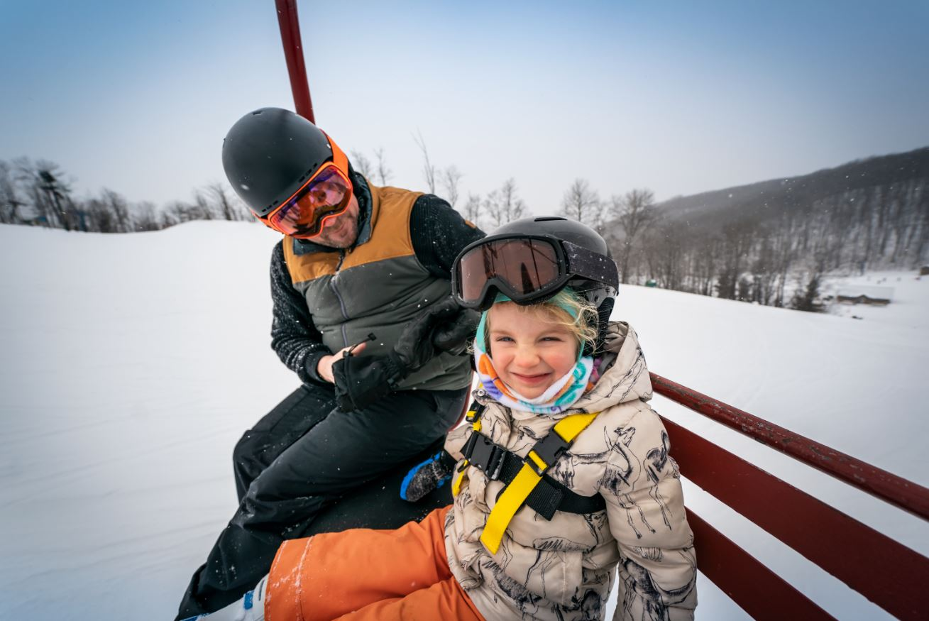 Child and parent on a ski/sledding slope