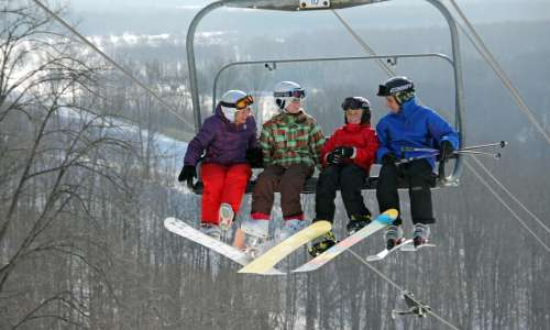 4 people on a ski chair lift