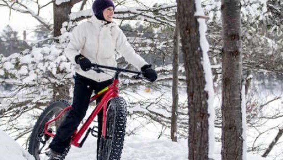 person riding a fat tire bike through a snowy forest