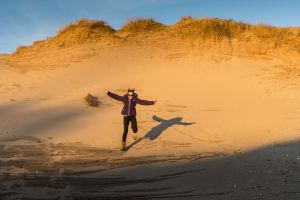 person running down a sand dune at Sleeping Bear Dunes National Lakeshore, Traverse City, MI