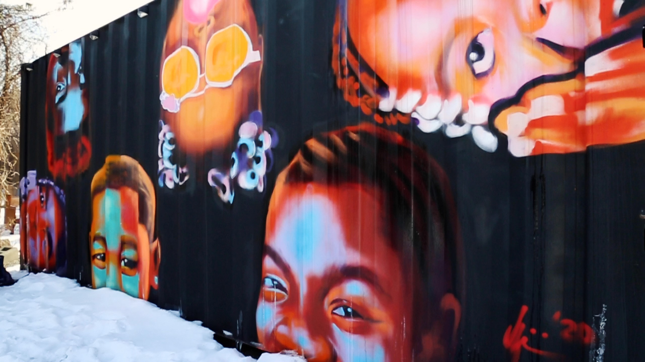 A decorated outdoor wall, with faces painted on it